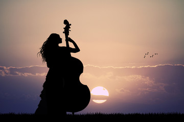 woman plays the double bass at sunset