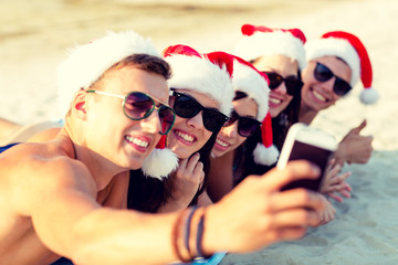 group of friends in santa hats with smartphone