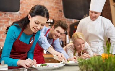 happy friends and male chef cooking in kitchen