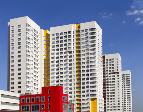 Multistory new modern apartment building against the blue sky. Stylish living block of flats. Newly built block of flats