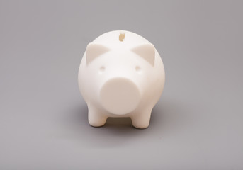 Piggy bank over gray background