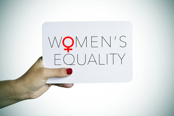 woman holds a signboard with the text womens equality