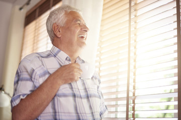 Elder man drinking coffee and looking through the window