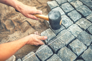 Close-up of construction worker installing and laying pavement stones on terrace, road or sidewalk. Worker using stones and rubber hammer to build stone sidewalk Wall mural