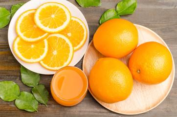 Slice of Navel orange fruit and juice on wooden background
