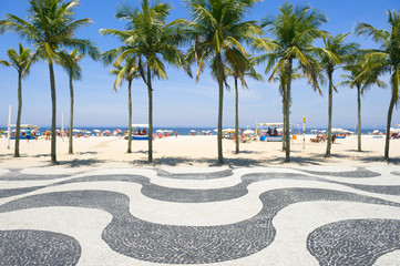 Iconic curving sidewalk tile pattern with palm trees at Copacabana Beach Rio de Janeiro Brazil