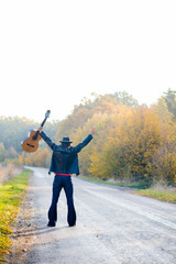 Picture of lonely guitarist looking at empty country road