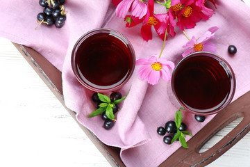 Glasses of fresh blackcurrant juice on wooden tray with pink napkin and flowers, top view