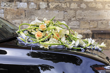 Wedding bouquet of white lilies and pink roses on the hood of the black car