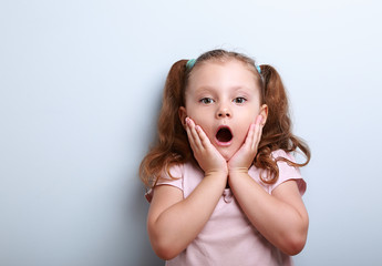 Fun surprising kid girl with opened mouth looking