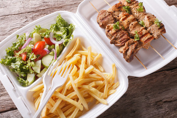 Lunch Box: kebabs, fries and fresh salad in tray close-up. Horizontal