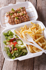 Lunch Box: kebabs, fries and fresh salad in tray close-up. vertical