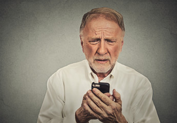 Worried elderly man looking at his smart phone