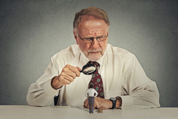businessman skeptically looking at small employee through magnifying glass