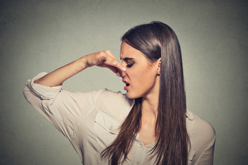 woman pinches nose looks with disgust something stinks bad smell