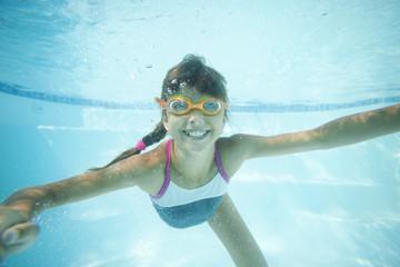 Joyful girl swimming underwater in pool