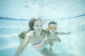Young mother and toddler son swimming underwater in pool and having fun