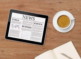 News page on tablet and coffee cup