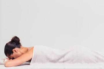 Woman lying on massage lounger