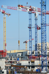 Construction cranes and site against a blue sky