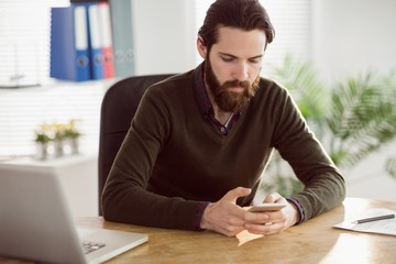 Hipster businessman sending a text