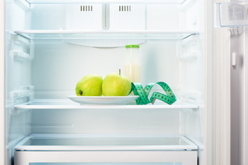 Two apples with measuring tape and glass bottle in refrigerator