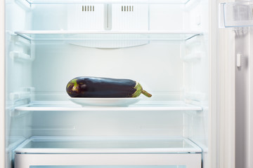 Purple eggplant on white plate in open empty refrigerator