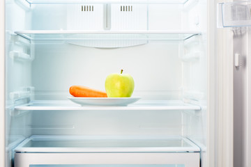 Green apple and orange carrot on white plate in refrigerator