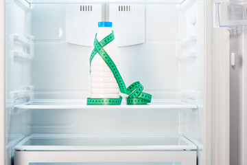 Bottle of yoghurt with measuring tape on shelf of refrigerator