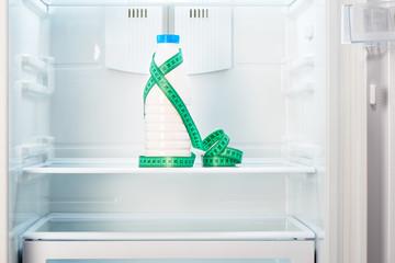 Bottle of yoghurt with measuring tape on shelf of refrigerator
