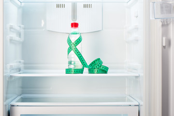 Bottle of water with measuring tape on shelf of refrigerator