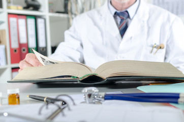 Doctor doing research in a medical book
