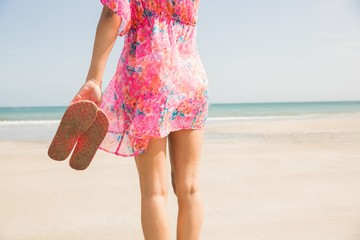 Stylish woman standing on the sand