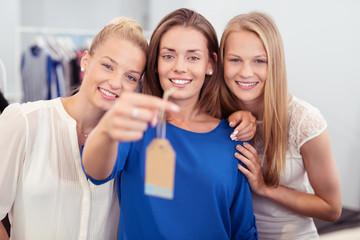 drei freundinnen beim shoppen in einer boutique zeigen ein schild