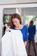 lächelnde frau schaut auf eine bluse in einer boutique