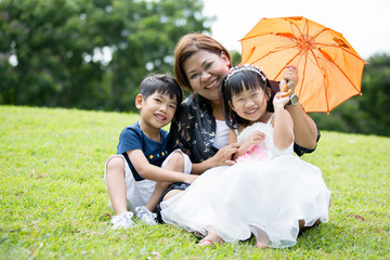 Happy Asian Family Enjoying Day In Park