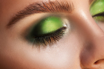 Close up photo of closed eyes with green makeup