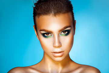 Fashionable young girl with green colors makeup and short hairst