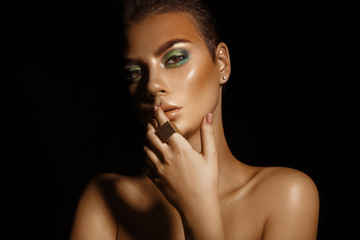 Glamour high contrast young woman with green colors makeup on bl