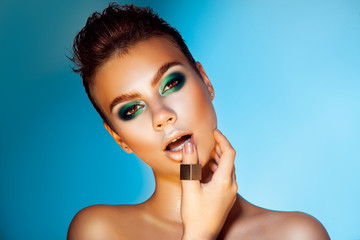 Voluptuous adult woman with green colors makeup on blue backgrou