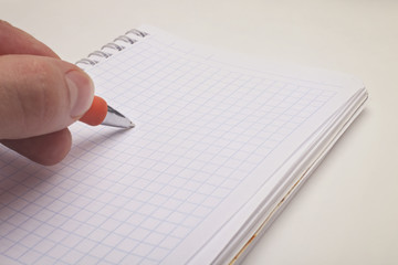 hand holding a ballpoint pen and notepad