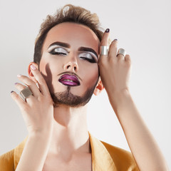 Sensual man with makeup and closed eyes in studio