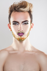 Vertical portrait of cutie young gay model with makeup and multi