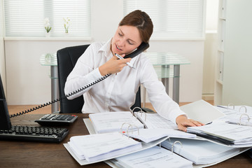 Businesswoman Using Telephone While Doing Accounting