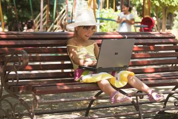 Девочка с ноутбуком на игровой площадке