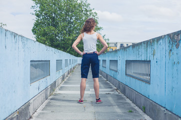 Young woman standing on a footbridge
