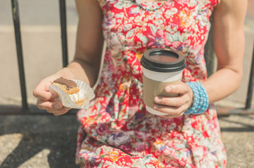 Young woman with coffee and cake outside
