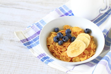 Breakfast cereal with blueberries, bananas and milk on a rustic