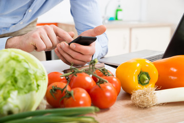 Person Hands Using Mobile Phone In Kitchen