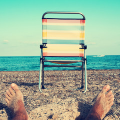 chair and young man on the beach, filtered